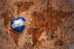 Heart with national flag of el salvador on a vintage world map crack paper background. Royalty Free Stock Photography
