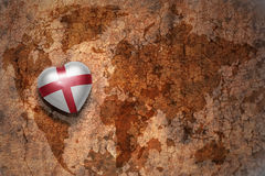 Heart with national flag of england on a vintage world map crack paper background. Royalty Free Stock Photography
