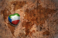 Heart with national flag of equatorial guinea on a vintage world map crack paper background. Royalty Free Stock Photos