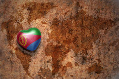 Heart with national flag of eritrea on a vintage world map crack paper background. Concept Royalty Free Stock Photography