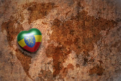 Heart with national flag of ethiopia on a vintage world map crack paper background. Concept Royalty Free Stock Image