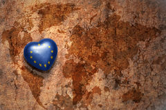 Heart with national flag of european union on a vintage world map crack paper background. Concept Royalty Free Stock Image