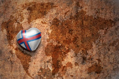 Heart with national flag of faroe islands on a vintage world map crack paper background. Concept royalty free stock photography