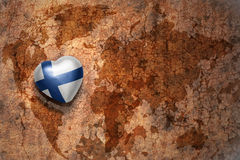 Heart with national flag of finland on a vintage world map crack paper background. Concept Stock Photo