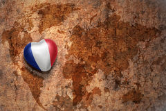 Heart with national flag of france on a vintage world map crack paper background. Concept Stock Photography