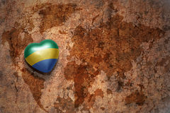 Heart with national flag of gabon on a vintage world map crack paper background. Concept Royalty Free Stock Images
