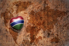 Heart with national flag of gambia on a vintage world map crack paper background. Concept Royalty Free Stock Photography