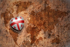 Heart with national flag of georgia on a vintage world map crack paper background. Stock Image