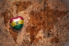 Heart with national flag of ghana on a vintage world map crack paper background. Concept Stock Images