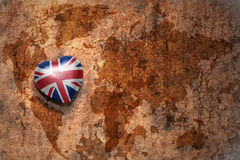 Heart with national flag of great britain on a vintage world map crack paper background Stock Photography