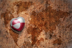 Heart with national flag of greenland on a vintage world map crack paper background. Concept Royalty Free Stock Image