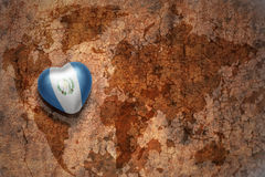 Heart with national flag of guatemala on a vintage world map crack paper background. Royalty Free Stock Photos