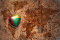 Heart with national flag of guinea bissau on a vintage world map crack paper background. Concept Stock Images