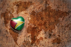 Heart with national flag of guyana on a vintage world map crack paper background. Royalty Free Stock Photo
