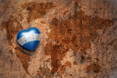 Heart with national flag of honduras on a vintage world map crack paper background. Stock Photo