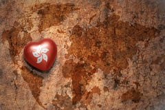 Heart with national flag of hong kong on a vintage world map crack paper background. Concept Stock Images