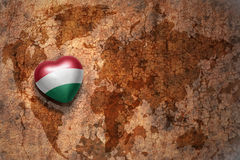 Heart with national flag of hungary on a vintage world map crack paper background. Concept Royalty Free Stock Images