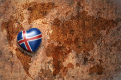 Heart with national flag of iceland on a vintage world map crack paper background. Concept Stock Photos