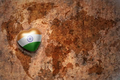 Heart with national flag of india on a vintage world map crack paper background. Concept royalty free stock photos