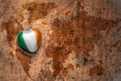 Heart with national flag of ireland on a vintage world map crack paper background. Concept Stock Photos