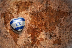 Heart with national flag of israel on a vintage world map crack paper background. Concept Stock Photos