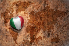 Heart with national flag of italy on a vintage world map crack paper background. Concept Stock Photo