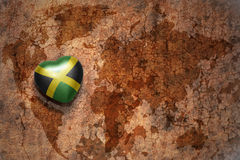 Heart with national flag of jamaica on a vintage world map crack paper background. Royalty Free Stock Image