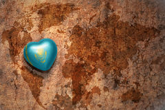 Heart with national flag of kazakhstan on a vintage world map crack paper background. Concept Royalty Free Stock Photo