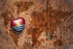 Heart with national flag of Kiribati on a vintage world map crack paper background. Concept Stock Photos