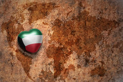 Heart with national flag of kuwait on a vintage world map crack paper background. Royalty Free Stock Image