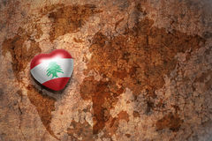 Heart with national flag of lebanon on a vintage world map crack paper background. royalty free stock photos