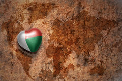 Heart with national flag of madagascar on a vintage world map crack paper background. Concept Royalty Free Stock Images