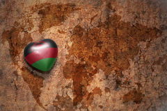 Heart with national flag of malawi on a vintage world map crack paper background. Royalty Free Stock Photos