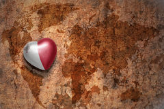 Heart with national flag of malta on a vintage world map crack paper background. Concept Stock Photos