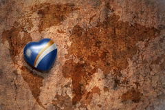 Heart with national flag of Marshall Islands on a vintage world map crack paper background. Concept Royalty Free Stock Photography
