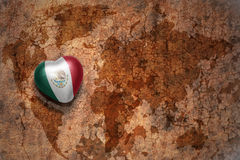Heart with national flag of mexico on a vintage world map crack paper background. stock photo