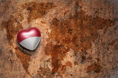 Heart with national flag of monaco on a vintage world map crack paper background. Concept Royalty Free Stock Image