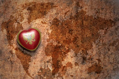Heart with national flag of montenegro on a vintage world map crack paper background. Concept Stock Photography