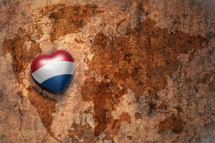 Heart with national flag of netherlands on a vintage world map crack paper background. Concept Royalty Free Stock Photos