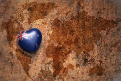 Heart with national flag of new zealand on a vintage world map crack paper background. Concept Royalty Free Stock Image