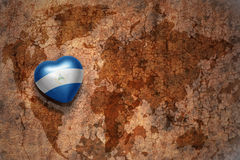 Heart with national flag of nicaragua on a vintage world map crack paper background. Stock Photography