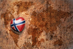 Heart with national flag of norway on a vintage world map crack paper background. Concept Stock Images