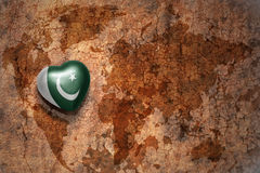 Heart with national flag of pakistan on a vintage world map crack paper background. Stock Photos