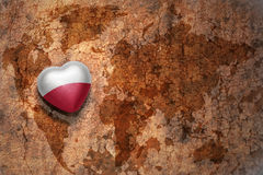 Heart with national flag of poland on a vintage world map crack paper background. Concept Stock Images