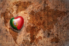 Heart with national flag of portugal on a vintage world map crack paper background. Concept Royalty Free Stock Image