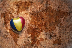 Heart with national flag of romania on a vintage world map crack paper background. Concept Stock Image