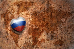Heart with national flag of russia on a vintage world map crack paper background. Concept Stock Photo