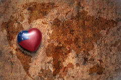 Heart with national flag of Samoa on a vintage world map crack paper background. Concept Stock Photo