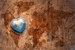 Heart with national flag of san marino on a vintage world map crack paper background. Concept Stock Images