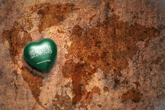 Heart with national flag of saudi arabia on a vintage world map crack paper background. Stock Photo